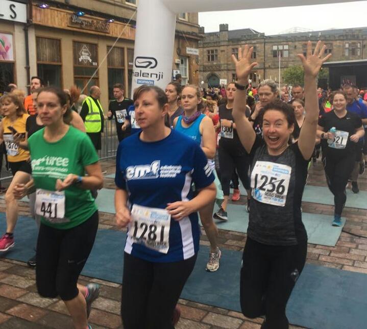 Three runners cross the start line at the Paisley 10k
