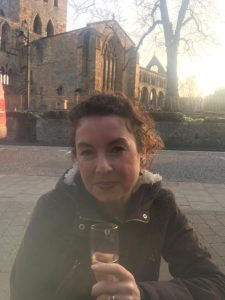 picture of woman with a glass of wine sitting in front of a ruined abbey