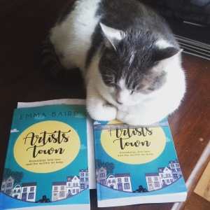 cat sitting on two copies of Artists Town